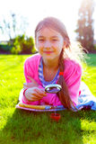 Girl looking through  magnifying glass on the grass Stock Images