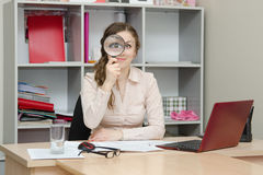 Girl looking through a magnifying glass in the office Royalty Free Stock Images