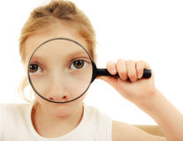 The girl looking through a magnifying glass. Royalty Free Stock Photography