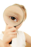 The girl looking through a magnifying glass. Stock Photo