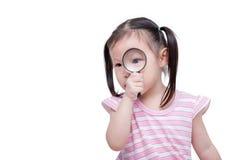 Girl looking through magsifying glass Royalty Free Stock Photos
