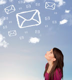 Girl looking at mail symbol clouds on blue sky Stock Photos