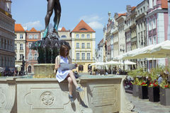 Girl looking at the map sitting by the fountain. At the main square Rynek of Poznan, Poland Stock Photos