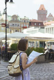 Girl looking at the map standing at the main square Rynek of Poz. Girl looking at the map standing at the main square Rynek of polish city Poznan Royalty Free Stock Photo