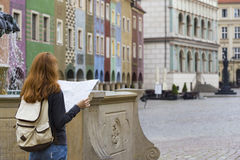 Girl looking at the map standing at the main square Rynek of Poz. Girl looking at the map standing at the main square Rynek of polish city Poznan Royalty Free Stock Photography