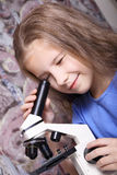 Girl looking through a microscope Royalty Free Stock Photos