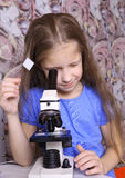 Girl looking through a microscope Stock Image