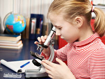 Girl looking through a microscope Stock Photo