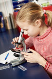 Girl looking through a microscope Royalty Free Stock Photo