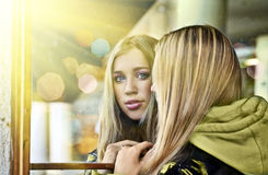 Girl looking from mirror. Blond girl looking from mirror stock image