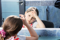 Girl looking at mirror. Little cute brunette girl looking at mirror Royalty Free Stock Image