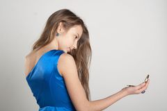 Girl looking into mirror. Girl in blue dress looking in mirror at studio stock photography