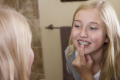 Girl looking in the mirror, examining her braces. Teen girl looking in the mirror, examining her braces Royalty Free Stock Photo