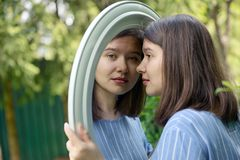 Girl looking in mirror. With nature background royalty free stock images