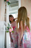 Girl  looking in the mirror. Girl in a pink dress looking in the mirror Royalty Free Stock Photography