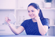 Girl looking in mirror. Girl satisfied with her appearance looking in mirror and smiling Stock Images