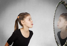 Girl looking in the mirror, sticking her tongue out Stock Photo