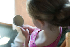 Girl Looking in Mirror. Young Girl Looking into Mirror on Sunny Day Royalty Free Stock Photography