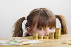 Girl looking at money. Girl looking at towers of money Stock Photo