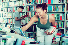 Girl looking for new literature. Happy teenager girl looking for new literature on shelves in book store Royalty Free Stock Images