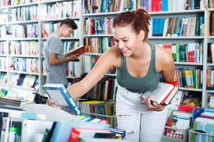 Girl looking for new literature. Happy teenager girl looking for new literature on shelves in book store Stock Photography
