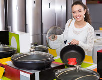 Girl looking for new pan and pot in supermarket Stock Photography
