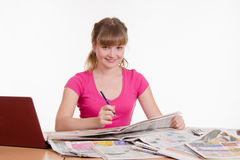 Girl looking in the newspaper classifieds Royalty Free Stock Photography