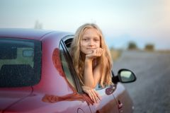 Girl looking out the car. Autotravel with children. happy smiling little girl looking out the car window and sunset at the background royalty free stock photos