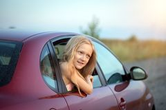 Girl looking out the car. Autotravel with children. happy smiling little girl looking out the car window and sunset at the background royalty free stock image