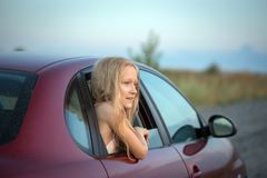 Girl looking out the car. Autotravel with children. happy smiling little girl looking out the car window and sunset at the background stock photography