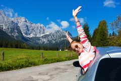 Girl looking out the car. Happy girl looking out the car window and mountains in the background. Dolomites, Italy stock image