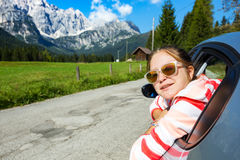 Girl looking out the car. Happy girl looking out the car window and mountains in the background. Dolomites, Italy stock photos