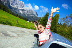 Girl looking out the car. Happy girl looking out the car window and mountains in the background. Dolomites, Italy royalty free stock photos