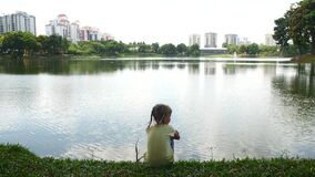 A girl is looking out for fish in a pond.