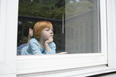 Girl Looking Out Through Glass Window Stock Photography