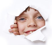 Girl looking out of a hole in a paper Stock Photography