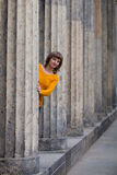 Girl looking out of old columns. Girl is looking out of old grey columns Stock Photos