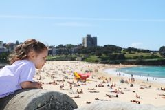 Girl looking out over summer beach scene. From the foreshore Stock Photos