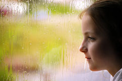 Girl looking out rainy window Stock Photos