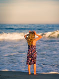 Girl looking out to sea at sunset. Young blond girl wearing patterned dress and with bare feet stands at water's edge looking out to sea at sunset in summertime Stock Photo