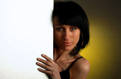 Girl is looking out-of the white empty board Royalty Free Stock Image