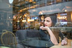 Girl looking out window in cafe Stock Images