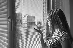 Girl looking out the window. The girl looks out the window through the blinds Stock Photography