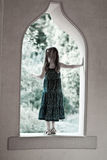 Girl looking out window in old Palace Garden royalty free stock photos