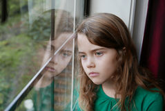 Girl looking out a window with a sad expression. Young, brunette, Caucasian girl looking through a window to the outside. Her face is reflecting in the window royalty free stock image