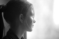 Girl looking out the window Stock Photography