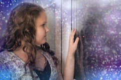 Girl looking out the window Royalty Free Stock Photos