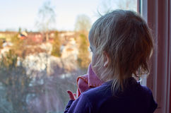 Girl Looking Out of A Window Royalty Free Stock Photography