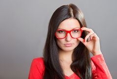 Girl looking over glasses. Portrait of a pretty serious girl looking over glasses, studio shot on gray background Royalty Free Stock Images