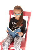 Girl looking over nerdy glasses reading a book Stock Images